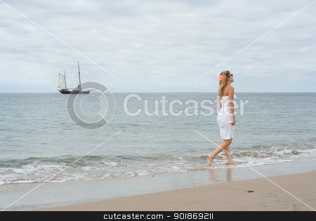 Girl in white dress on the coast with old ship in the background stock photo, Girl in white dress on the coast with old ship in the background by Alexander Tarasov
