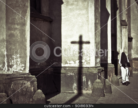 Church and nun stock photo, Dark and mystical atmosphere with a nun entering in a church by tristanbm