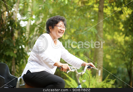 Active senior stock photo, 60s senior Asian woman riding on bicycle outdoor with great fun by szefei
