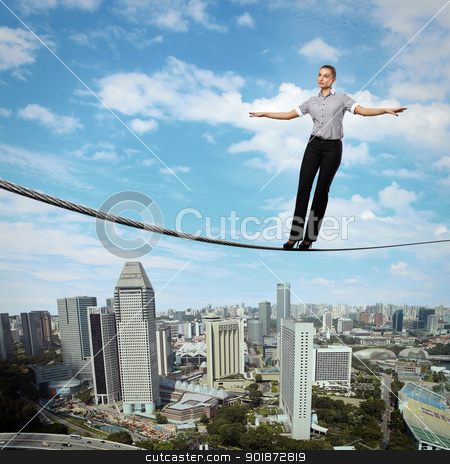 Balancing businesswoman and cityscape stock photo, Business woman balancing high over a cityscape  by Sergey Nivens
