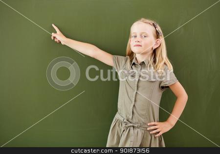 Scoolgirl standing near blackboard stock photo, Scoolgirl standing in class near a green blackboard by Sergey Nivens