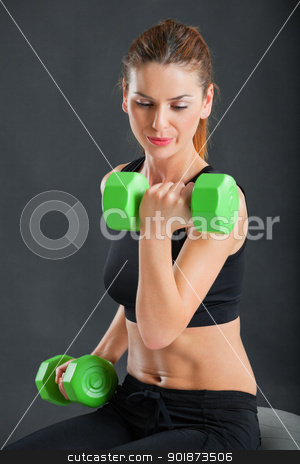 Training with weights stock photo, Photo of an attractive female doing dumbbell curls while sitting on an exercise ball.  by © Ron Sumners