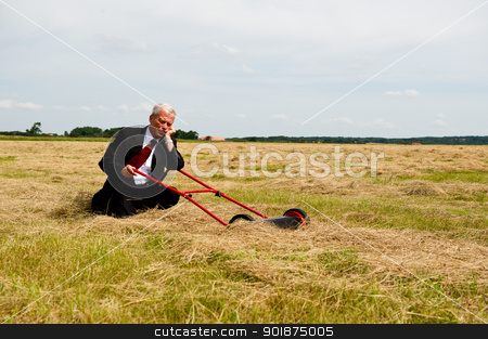 Reaping the rewards stock photo, An exhausted businessman rest on his knees with his lawnmower in a field of harvested grain as he prepares to reap the rewards of all his hard labour and perseverance, conceptual image by Instudio 68