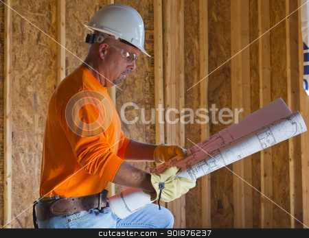 Male Construction Worker stock photo, A male construction worker reads blueprints while working at a construction site by Walter Arce