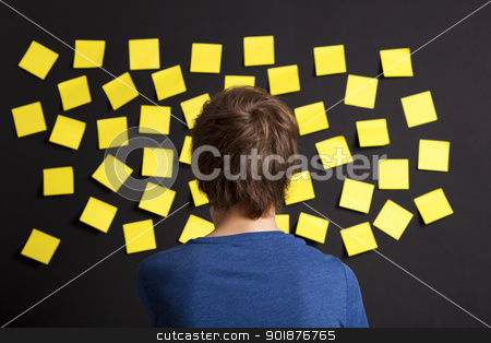 Looking to yellow reminders stock photo, Young student looking to a board full of yellow notes by ikostudio