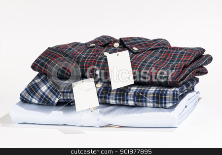 Stack of folded shirts stock photo, Stack of folded shirts with blank label by pixs4u
