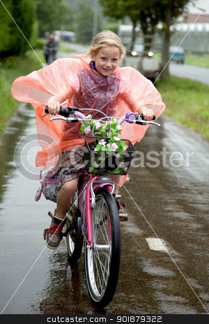 girl cycling in the rain stock photo, girl with plastic poncho cycling in the rain by anton havelaar