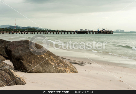 Big stone in sand on beach with jetty stock photo, Big stone in sand on beach with jetty and cloud in evening time by moggara12