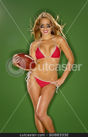 Blonde Model With Football stock photo, A blonde model posing with a football in a studio environment by Walter Arce