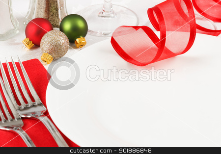 Christmas Table Setting stock photo, Holiday ornaments decorate a restaurant table setting in festive red and green Christmas colors with copy space on an empty white plate by Karen Sarraga