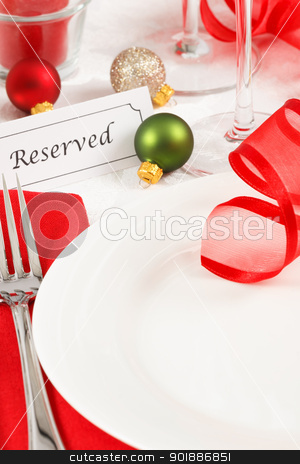 Reserved Christmas Table Setting stock photo, A festive red and green Christmas table setting is adorned with ribbon and ornaments leaving copy space on a white plate by Karen Sarraga