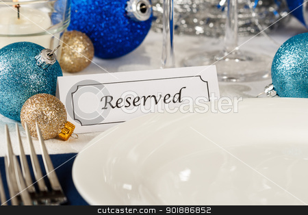 Reserved Holiday Table Setting stock photo, Close up view of a holiday table setting with an empty plate providing copy space is decorated with blue and gold ornaments and a placard showing a reserved place by Karen Sarraga
