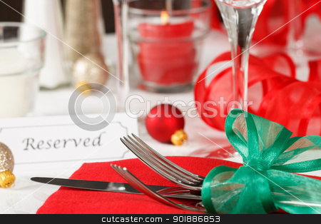 Reserved Christmas Restaurant Table stock photo, Close up view of a holiday table setting with red and green decorations and placard showing a reserved space by Karen Sarraga
