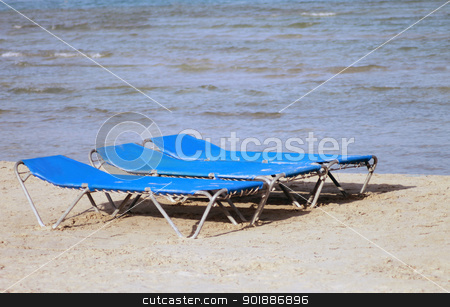 Sun loungers or beds on beach stock photo, Sun loungers or beds on sandy beach, summer holiday scene. by Martin Crowdy