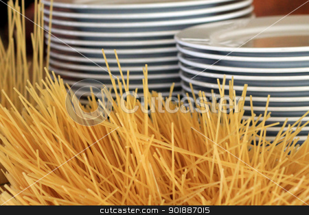 Pasta and stacks of plates stock photo, Pasta and stacks of plates in restaurant, food background. by Martin Crowdy