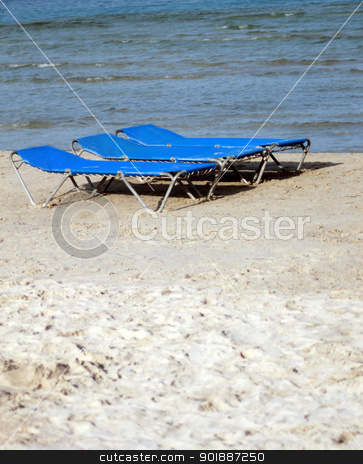 Sun loungers or beds on sandy beach stock photo, Sun loungers or beds on sandy beach in summer. by Martin Crowdy