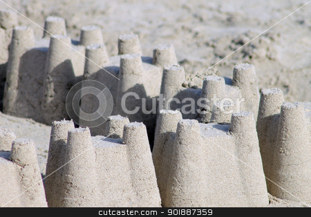 Sand castles on beach stock photo, Rows of sand castles on sandy beach with copy space. by Martin Crowdy