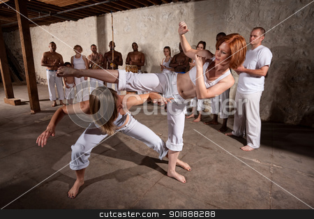 Pair of Capoeria Performers Fighting stock photo, Capoeria martial artists performing techniques on concrete floor by Scott Griessel