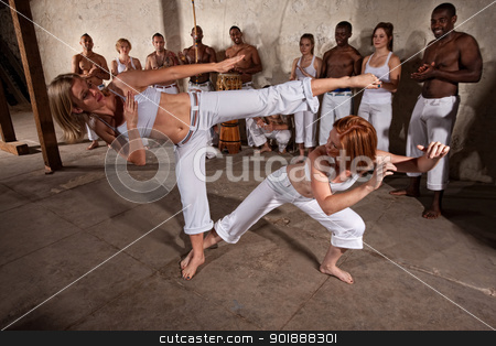 Capoeria Fighters Demonstrating Martial Arts stock photo, Young woman evades a kick during a Capoeira demonstration by Scott Griessel