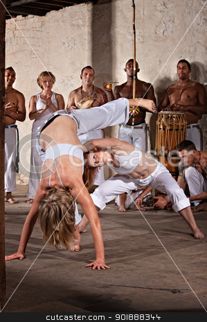 Female Capoeria Performers stock photo, Pair of female capoeira practitioners performing with group by Scott Griessel