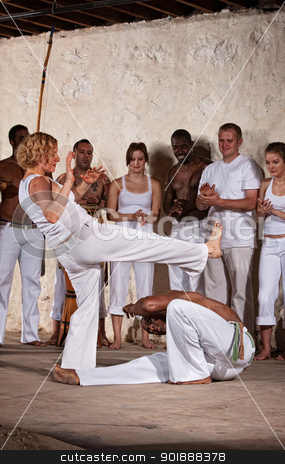 Capoeria Fighting stock photo, Woman throws a front kick as young man dodges during Capoeria practice by Scott Griessel