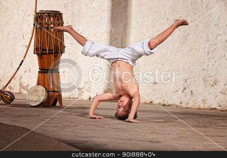 Young Male Martial Artist stock photo, Cute capoeria boy in headstand with African music instruments by Scott Griessel
