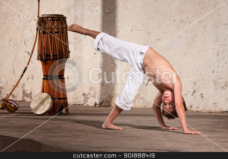 Serious Young Capoeira Student stock photo, Young capoeria martial artist next to berimbau on floor by Scott Griessel