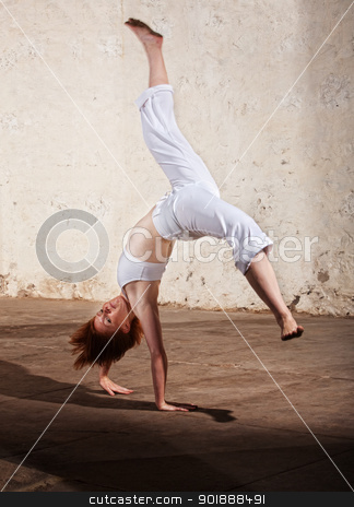 Capoeria Cartwheel Demonstration stock photo, Young woman performing a cartwheel on floor by Scott Griessel