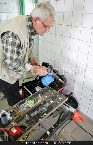 Grey-haired handyman using blow torch stock photo, Grey-haired handyman using blow torch by photography33