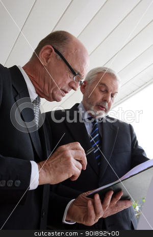 Two senior businessmen looking over a document stock photo, Two senior businessmen looking over a document by photography33