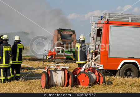 Burning round baler stock photo, Firefighters extinguish a burning round baler on a field by Harry Huber