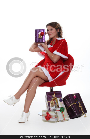 Woman dressed as Mrs. Claus holding a present stock photo, Woman dressed as Mrs. Claus holding a present by photography33