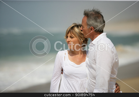 Married couple dressed in white taking a walk along the beach stock photo, Married couple dressed in white taking a walk along the beach by photography33