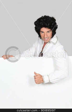 Man in an Elvis outfit and a board left blank for your image stock photo, Man in an Elvis outfit and a board left blank for your image by photography33