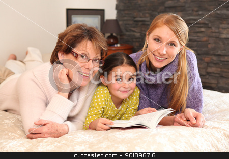 Grandmother, mother, and daughter lying on a bed stock photo, Grandmother, mother, and daughter lying on a bed by photography33