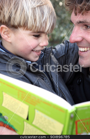 Man with little boy reading book outdoors stock photo, Man with little boy reading book outdoors by photography33