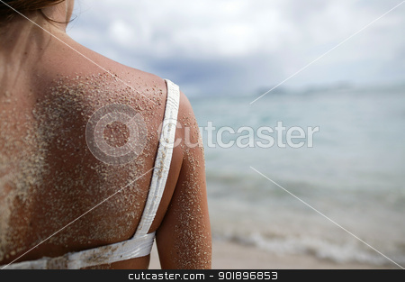 Woman stood on a beach with sand on her shoulder stock photo, Woman stood on a beach with sand on her shoulder by photography33