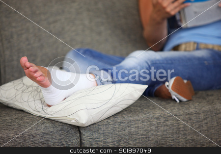 Woman with sprained ankle reading on the sofa stock photo, Woman with sprained ankle reading on the sofa by photography33
