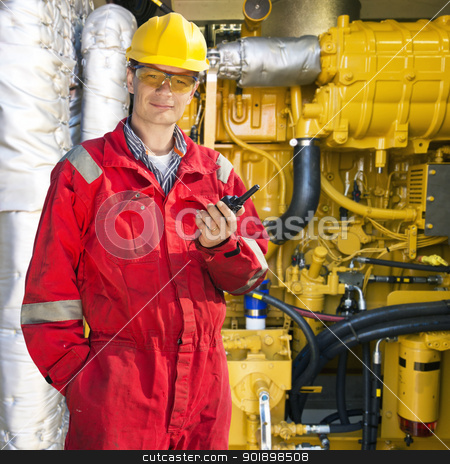 Engine room engineer stock photo, Engineer, wearing overalls, hard hat and safety goggles, posing in front of a huge hydraulic engine, hoding a wireless communication device in his hnd by Corepics VOF