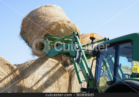 Tractor moving hay bales stock photo, Tractor moving hay bales by photography33