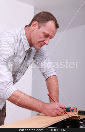 Man marking a floorboard with a pencil stock photo, Man marking a floorboard with a pencil by photography33
