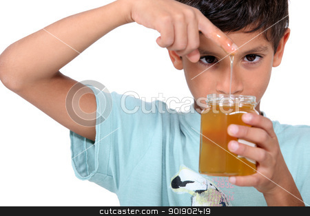 Boy playing with honey stock photo, Boy playing with honey by photography33