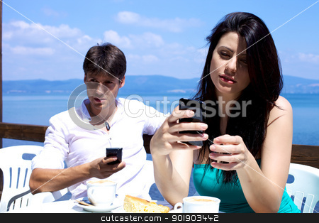 Boyfriend and girlfriend texting during breakfast stock photo, Couple texting with cellphones on a lake by federico marsicano