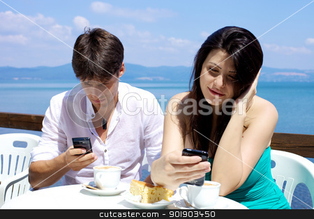 Couple texting having breakfast in front of lake stock photo, Happy couple texting with mobile phone during breakfast with cappuccino and cake on the lake by federico marsicano