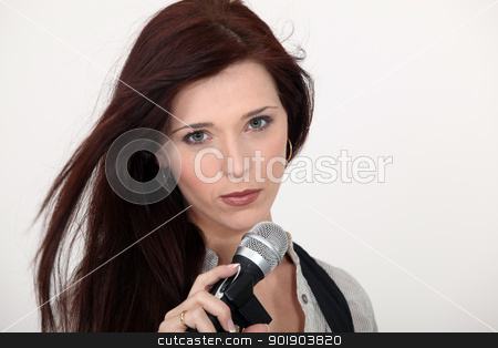 Brunette singer holding microphone stock photo, Brunette singer holding microphone by photography33