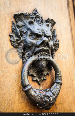 Devil Head Door Knocker stock photo, Door knoker on an old wodden door in Tuscany - Italy by Perseomedusa