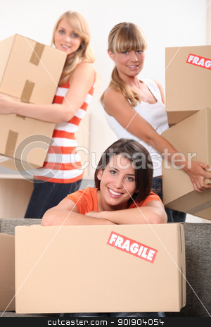 Three young women moving cardboard packing boxes marked fragile stock photo, Three young women moving cardboard packing boxes marked fragile by photography33