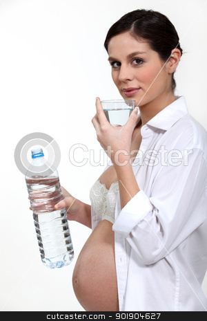 Pregnant woman drinking water stock photo, Pregnant woman drinking water by photography33