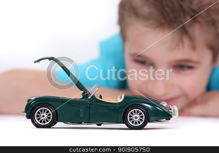 Little boy watching a toy car stock photo, Little boy watching a toy car by photography33