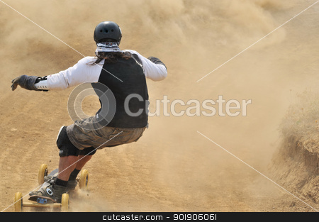 Mountain Boarder stock photo, Rear view at mountain boarder riding down through dust by zagart